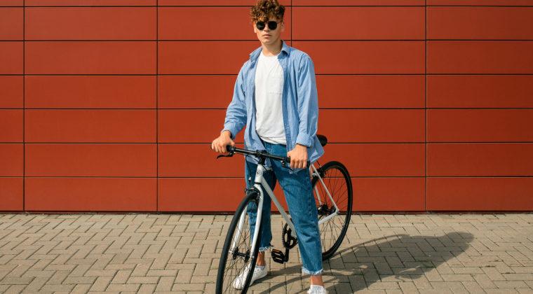 artikkelikuva jossa nuori mies polkupyöränsä kanssa